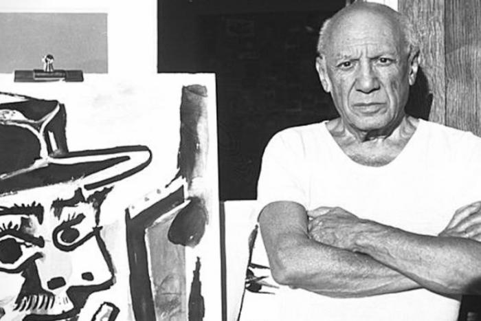 ο Πάμπλο Πικάσσο σε μεγάλη ηλικία ποζάρει δίπλα από ένα πίνακα του