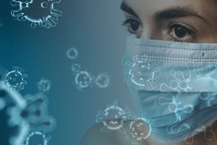 γυναίκα που φοράει χειρουργική μάσκα και αιωρούνται στο πλάι της σχήματα του ιού
