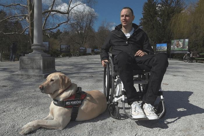 Ο Λούκα Πλάβτσακ σε αναπηρικό αμαξίδιο δίπλα του κάθεται σκύλος φοράει ειδικό τζάκετ για αμαξίδιο