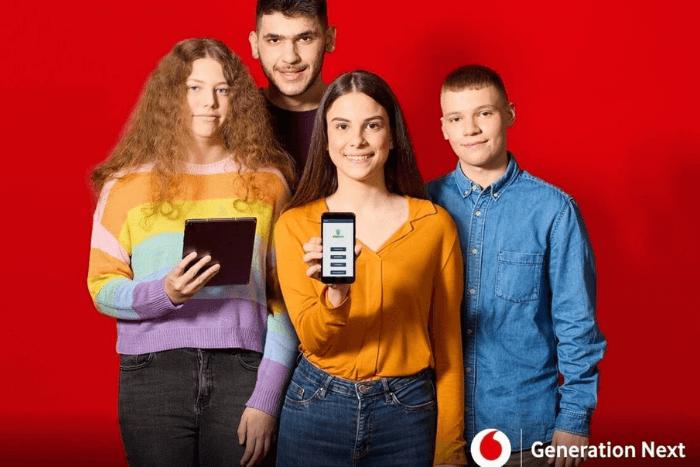 Οι μαθητές: Μαρία Κωστάκη, Αποστόλης Μηλιώτης, Κατερίνα Τεντολούρη και Βαγγέλης Τσίπρας. Η μια μαθήτρια κρατάει στο κινητό και δείχνει την εφαρμογή. Τα παιδιά φωτογραφίζονται σε κόκκινο φόντο της Vodafone.