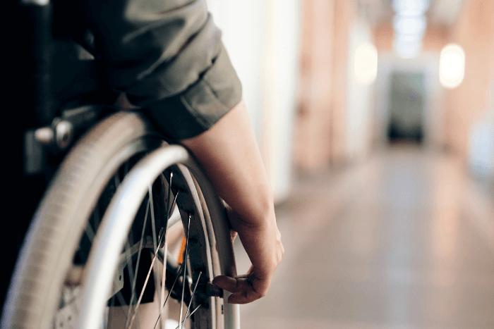 άτομο με αναπηρία σε αμαξίδιο κοντινό σε χέρι και ρόδα