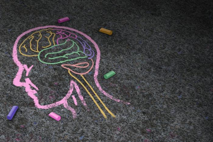 Κεφάλι ανθρώπου ζωγραφισμένο με κιμωλία σε οδόστρωμα και ο εγκέφαλος διάφορα κομμάτια χρωματιστά