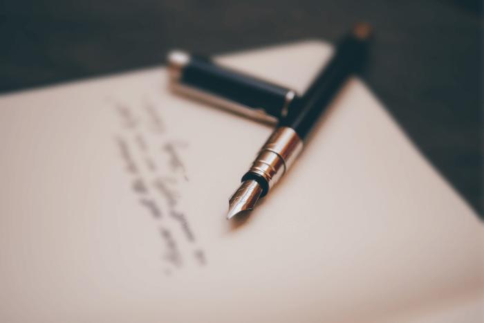 πένα που είναι ακουμπισμένη σε γραμμένο χαρτί