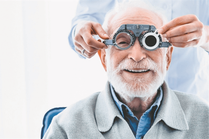 Ηλικιωμένος άνδρας σε οφθαλμίατρο, φοράει ειδικά γυαλιά για εξέταση.