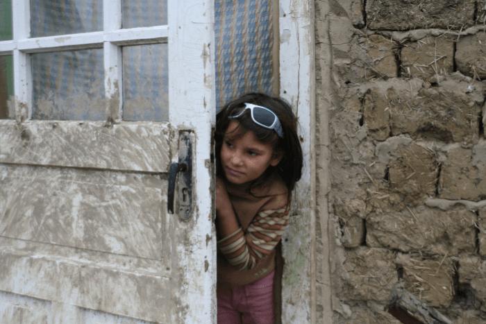 Παιδί ρομά που βρίσκεται σε σπίτι και κοιτάει έξω από την πόρτα