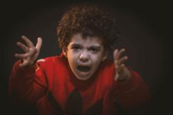 Αγόρι 10 ετών περίπου που είναι θυμωμένο με τα χέρια ψηλά και φωνάζει