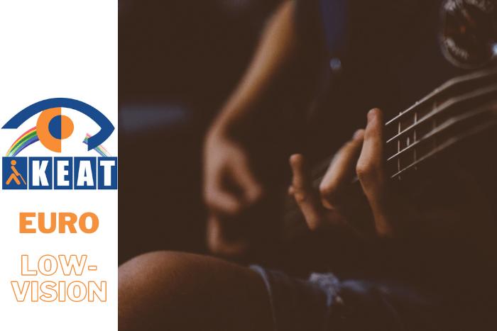 Νεαρό άτομο με κιθάρα στα χέρια παίζει μουσική φαίνονται μόνο τα χέρια του. Και στην αριστερή πλευρά το λογότυπο του ΚΕΑΤ.