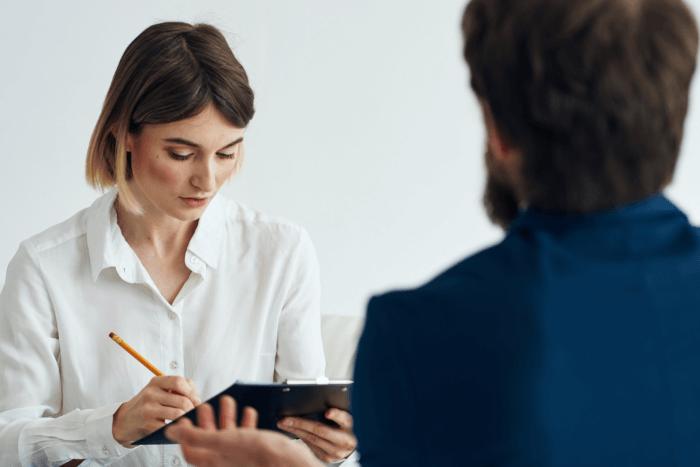 Γυναίκα σε ρόλο ψυχοθεραπευτή κρατάει σημειώσεις και άνδρας απέναντι της
