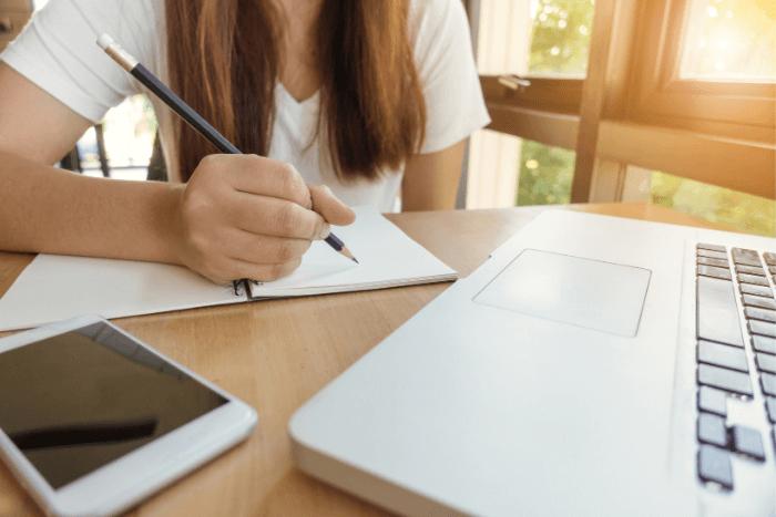 Μαθήτρια μπροστά σε λάπτοπ που σημειώνει και δίπλα της έχει κινητό τηλέφωνο (φαίνεται από το λαιμό και κάτω)