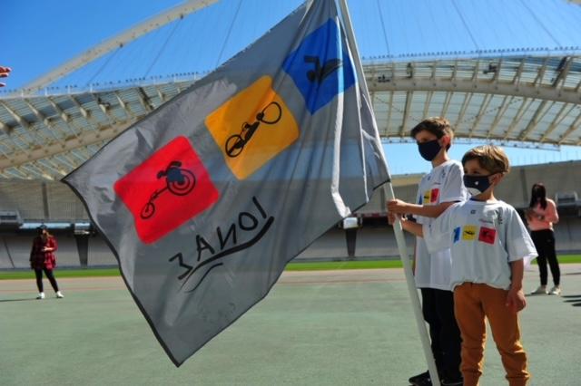 Παιδιά που κρατάνε τη σημαία του συλλόγου Ιωνά
