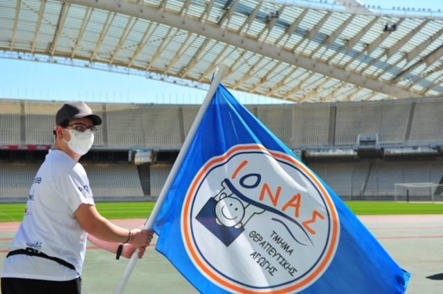 Αθλητής που κρατάει τη σημαία του συλλόγου Ιωνά