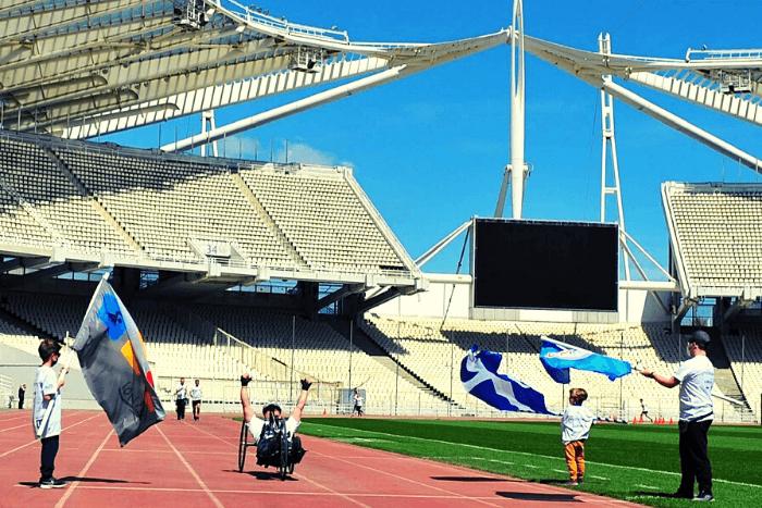 αθλητής με αμαξίδιο τρεξίματος τερματίζει ενώ τον περιμένουν παιδιά με σημαία του συλλόγου Ιωνά και ελληνική σημαία.