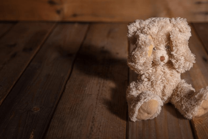 λούτρινο αρκουδάκι που έχει τα χέρια του στα μάτια του ακουμπισμένο σε ξύλινο πάτωμα