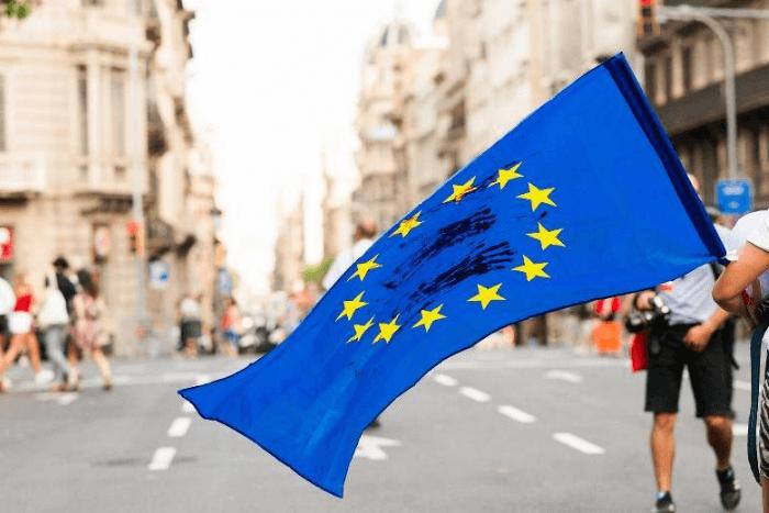 σημαία της Ευρωπαϊκής Ένωσης που την κρατάει ένα άτομο σε κεντρικό δρόμο