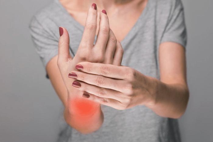 γυναίκα που κρατάει την παλάμη της και με κόκκινο χρώμα έχει τονιστεί το σημείο του καρπού που νιώθει τον πόνο