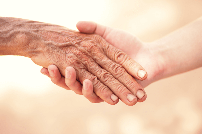 χέρι νεαρού ατόμου κρατάει χέρι ηλικιωμένου
