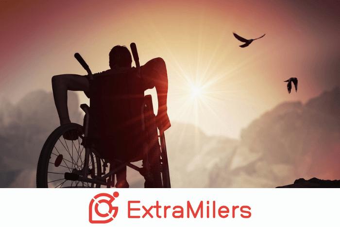 άτομο σε αναπηρικό αμαξίδιο σε εξωτερικό χώρο μπροστά σε ηλιοβασίλεμα και το λογότυπο του ExtraMilers