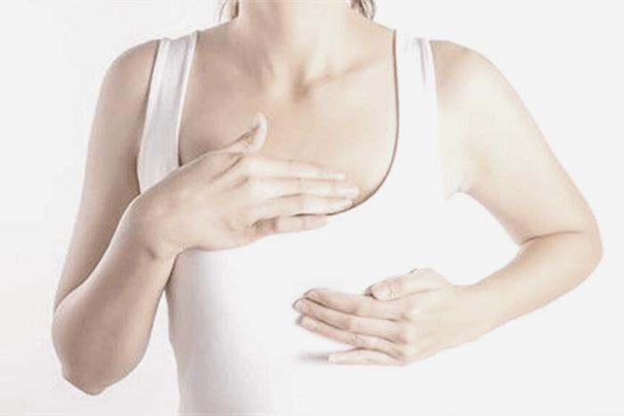 Γυναίκα με λευκό τοπ που κάνει την κίνηση ότι ψηλαφίζει τ στήθος της