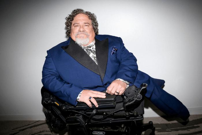 Ο Jim LeBrecht με μια κάμερα μπροστά του και με κοστούμι από τον Gucci. Είναι σκούρο μπλε με μαύρα σατέν πέτα και ένα floral μεταξωτό πουκάμισο - όλα σχεδιασμένα με γνώμονα την αναπηρία του.