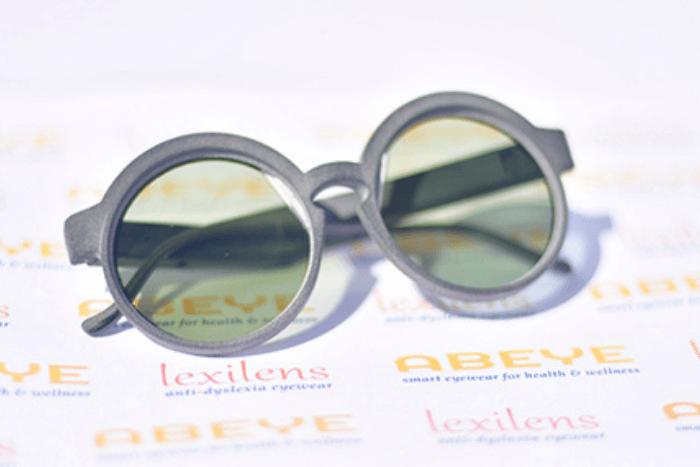 """Τα γυαλιά Lexilens πάνω σε χαρτί που αναγράφει την εταιρεία """"Abeye"""" και την ονομασία """"Lexilens"""""""