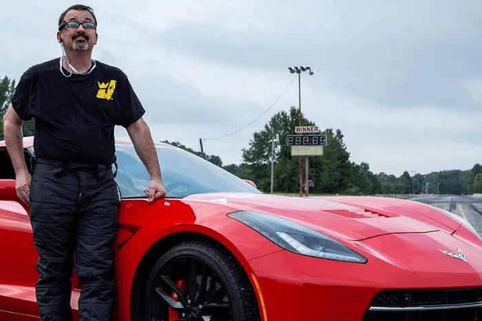 Ο Dan Parker όρθιος μπροστά από την κόκκινη Chevrolete Corvette C6