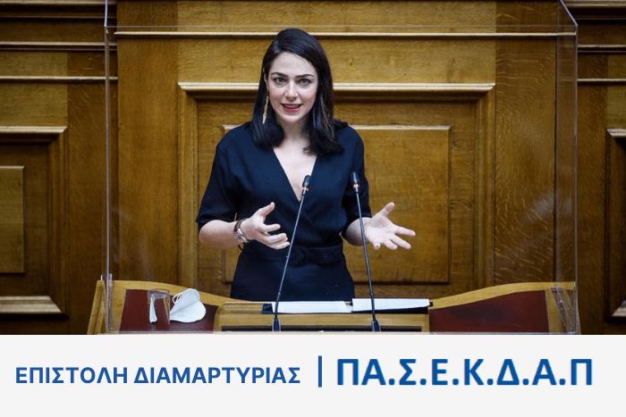 Η Δόμνα Μιχαηλίδου σε έδρανο της βουλής μιλάει. Κάτω από τη φώτο η φράση Επιστολή Διαμαρτυρίας ΠΑΣΕΚΔΑΠ.