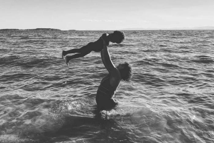 ασπρόμαυρη φωτογραφία μητέρας μέσα στη θάλασσα που κρατάει ψηλά στον αέρα το παιδί της