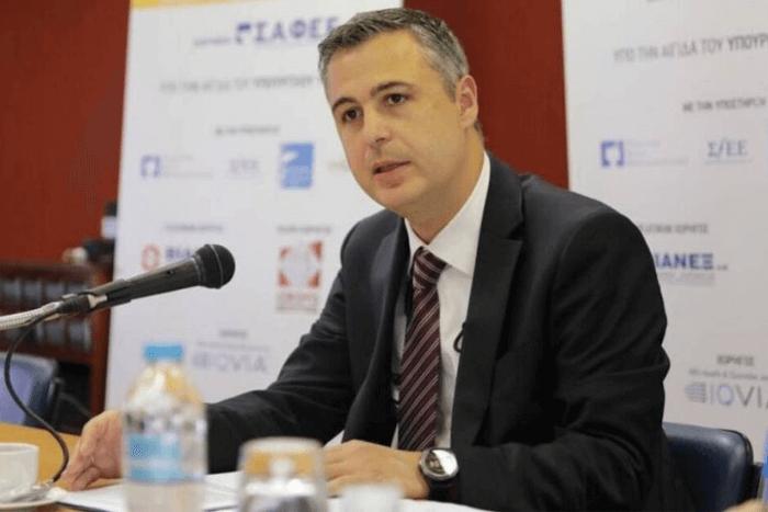 Γιάννης Κωτσιόπουλος καθιστός μπροστά σε επιτραπέζιο μικρόφωνο μιλάει