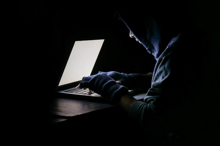 έφηβος μπροστά σε λάπτοπ σε σκοτεινό δωμάτιο και φορώντας κουκούλα και κομμένα γάντια γράφει σε υπολογιστή