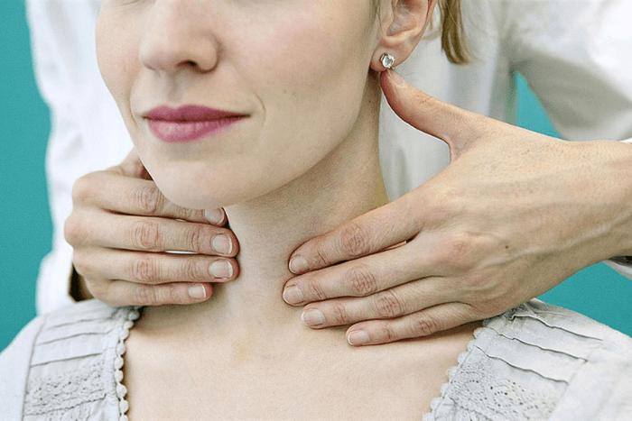 Γιατρός που κάνει ψηλάφηση σε λαιμό γυναίκας
