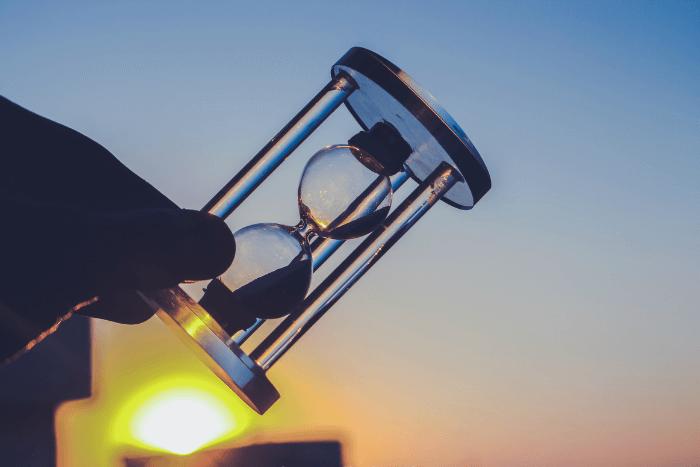 Άτομο κρατάει μια κλεψύδρα στο χέρι πλάγια γυρισμένη σαν να έχει για λίγο σταματήσει. Στο φόντο βλέπουμε ένα ηλιοβασίλεμα.