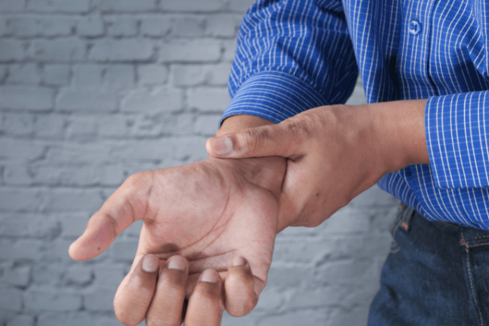 άνδρας που με το χέρι του τρίβει τον καρπό του άλλου χεριού