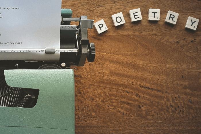 """Στη φωτογραφία απεικονίζεται μισή γραφομηχανή (σε ανοιχτό πράσινο χρώμα) με μισό φύλλο χαρτί και δίπλα γραμμένη με πλακίδια η λέξη """"poetry"""""""