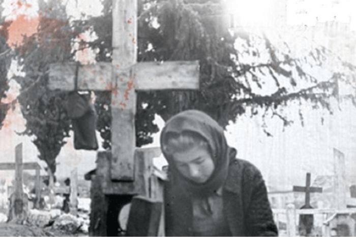 Γυναίκα μαυροφορεμένη σκυμμένη πάνω σε τάφο μπροστά από σταυρό. Πίσω της φαίνονται και άλλοι σταυροί από το Νεκροταφείο.