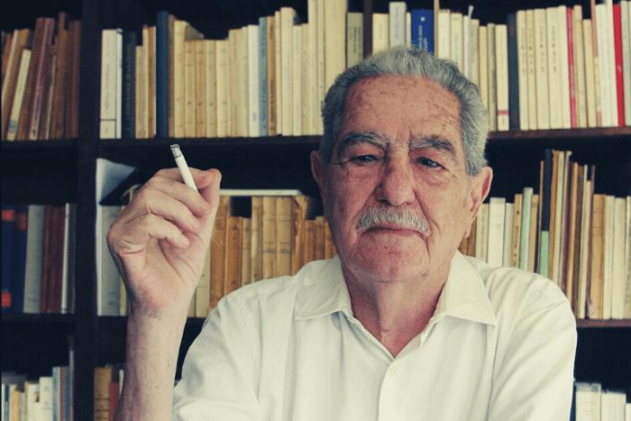 Ο Κώστας Αξελός μπροστά στην βιβλιοθήκη του κρατώντας τσιγάρο