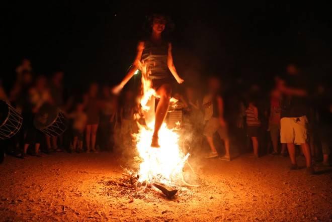 γυναίκα πηδάει από αναμμένη φωτιά γύρω γύρω κόσμος παρακολουθεί