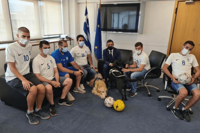 Ο Γενικός Γραμματέας Γιώργος Σταμάτης και αθλητές από την ποδοσφαιρική ομάδα τυφλών. Στην παρέα υπάρχει κι ένας σκύλος οδηγός τυφλών.