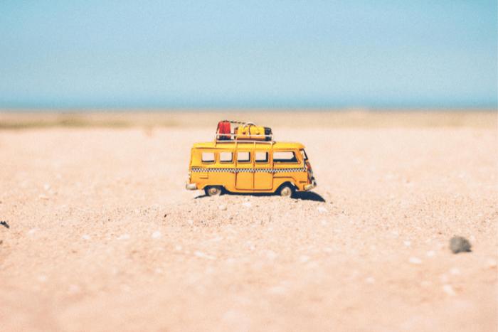 Μινιατούρα από βανάκι με αποσκευές στην οροφή η οποία βρίσκεται πάνω στην άμμο και στο βάθος θάλασσα.