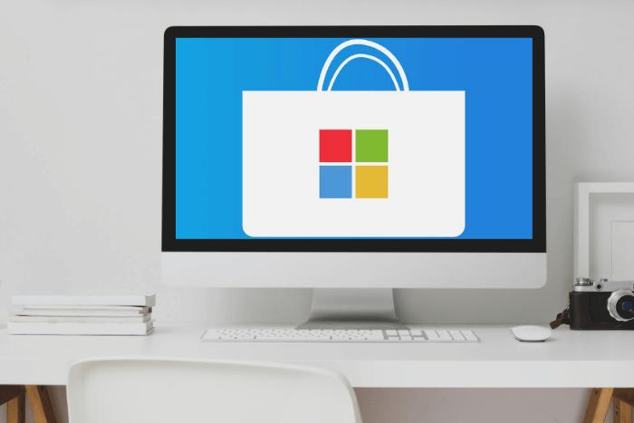 Υπολογιστής σε γραφείο όπου η οθόνη του δείχνει το λογότυπο του Microsoft Store: 4 Πολύχρωμα τετραγωνάκια μέσα σε μια τσάντα.