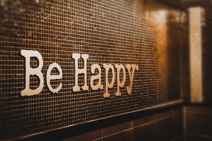 """τοίχος με πλακάκια που πάνω έχει ανάγλυφα γράμματα """"Be Happy"""""""