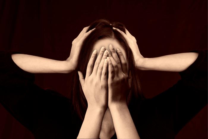 Γυναίκα που έχει δύο χέρια μπροστά στο πρόσωπό της και άλλα δύο χέρια που πιάνει το κεφάλι της με απόγνωση.