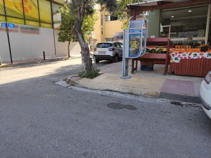 Ράμπα πεζοδρομίου που εμποδίζεται από καρτοτηλέφωνο, μπροστά από κατάστημα