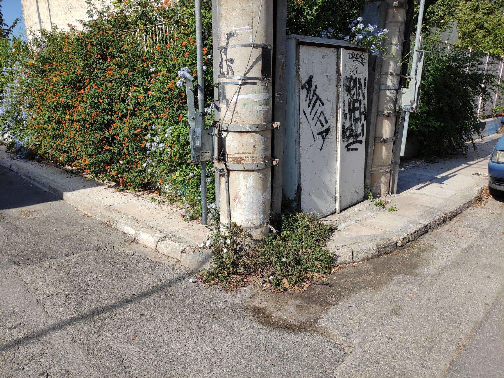 Μια κολώνα της ΔΕΗ πάνω σε γωνία στενού πεζοδρομίου.