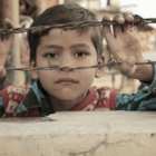 Μικρό αγόρι που κοιτάει από συρματόπλεγμα σε καταυλισμό