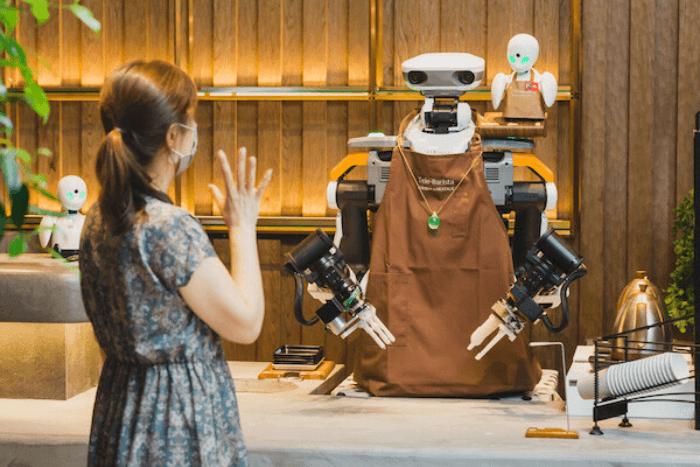 Γυναίκα είναι μπροστά σε ρομποτ σερβιτόρο και τον χαιρετάει