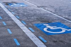 Πάρκινγκ στάθμευσης Ατόμων με αναπηρία με διαγράμμιση και αναπηρικό σήμα στην άσφαλτο.
