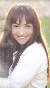 Έλλη Μερκούρη, χαμογελαστή με λευκή μπλούζα και μακριά μαλλιά