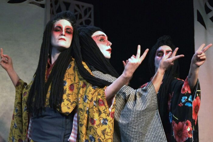 """Εικόνα από την παράσταση """"Ιστορίες φαντασμάτων από την Ιαπωνία"""". 3 γυναίκες με ιαπωνική πολύχρωμη ενδυμασία, οι 2 γυρισμένες ακουμπιούνται πλάτη-πλάτη και κάνουν νοήματα"""