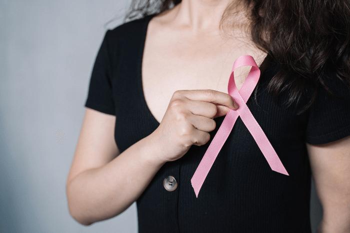 Γυναίκα με μαύρη μπλούζα κρατάει ροζ κορδέλα στο σημείο του στήθους