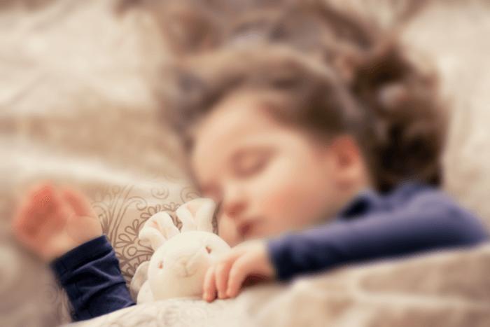Παιδί που κοιμάται ενώ στο ένα του χέρι κρατάει λούτρινο κουνελάκι